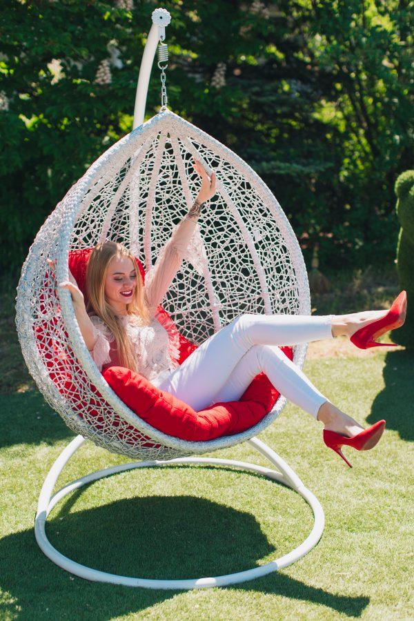 Белое подвесное кресло с красной подушкой радость девушки