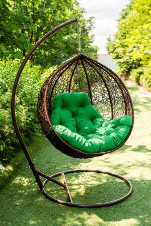 кресло кокон с зелёной подушкой из ротанга