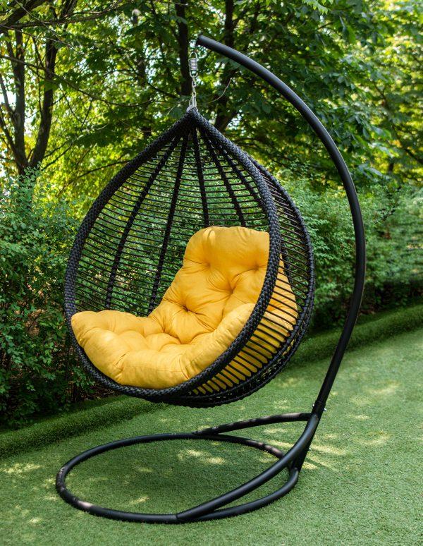 чорне підвісне крісло з жовтою подушкою