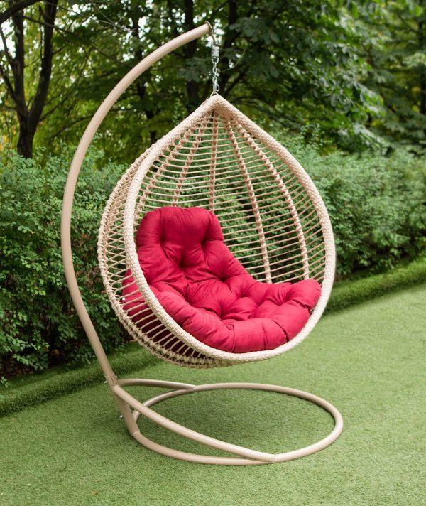крісло підвісне в кольорі беж і червоною подушкою