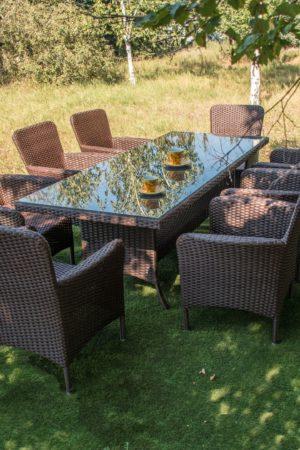Большой стол со стеклом и стулья из ротанга